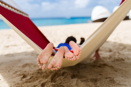 51368846 - brother and sister kids relaxing in hammock at tropical beach